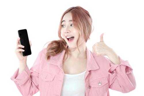 女性が携帯にグッドポーズをしている画像
