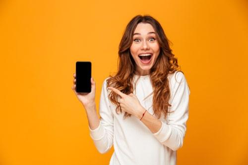 女性が携帯に指を指している画像