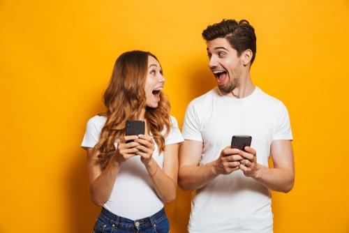 女性と男性が携帯を持っている画像