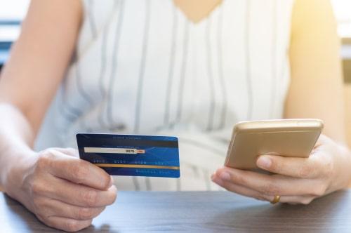 女性がクレジットカードを持っている画像