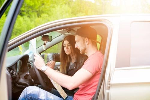 車で男性と女性が旅行計画を立てている様子