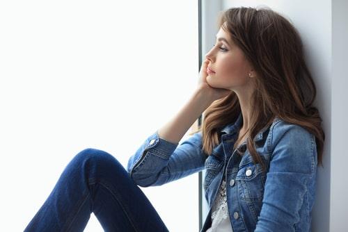 女性が窓際で考え事してる画像