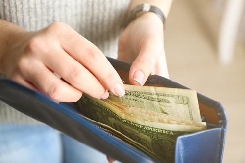 女性がお金を払おうとしている画像