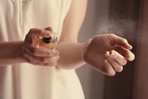 女性が香水をかけている画像