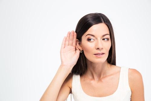 女性が耳をすましている画像