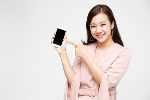 女性が携帯電話を見せびらかしている画像