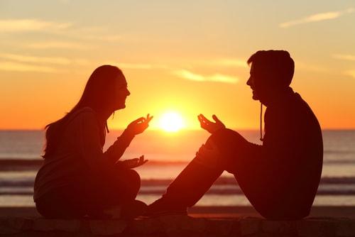 海辺で楽しそうに話している男女