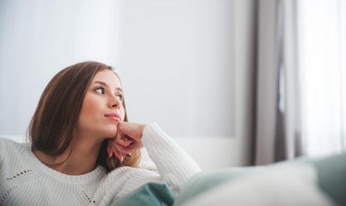 部屋で考え事をしている女性