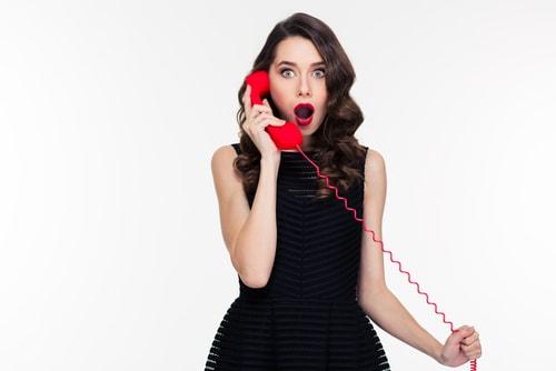 受話器を耳にあて何かに驚いてこっちを見ている女性