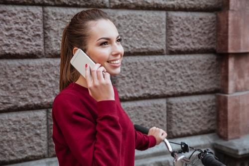 外で笑いながら電話をしている女性