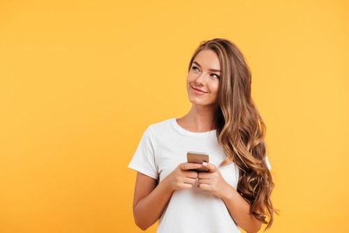 携帯電話を持って笑っている女性