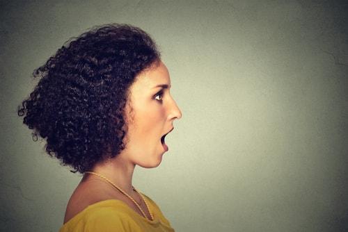 横を向いて口を開けている女性