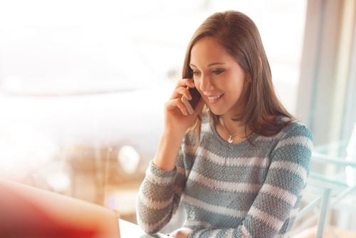 電話をしながら笑顔を見せている女性