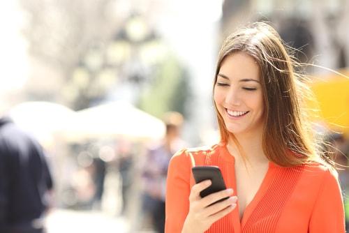 携帯電話を見て喜んでいる女性