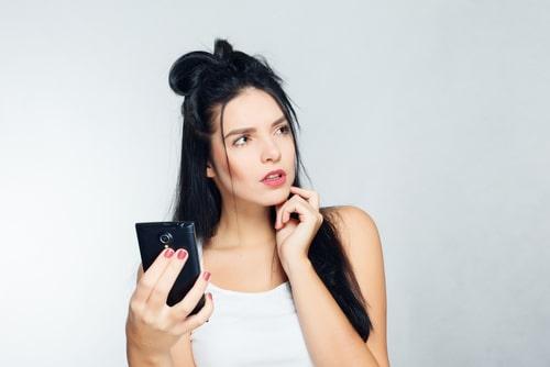 女性が携帯を持ちながら何かに悩んでいる様子