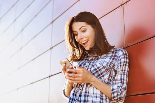 携帯を見て喜んでいる女性