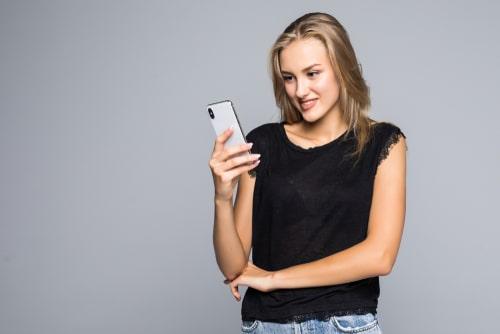 立ちながら携帯を操作している外国人女性