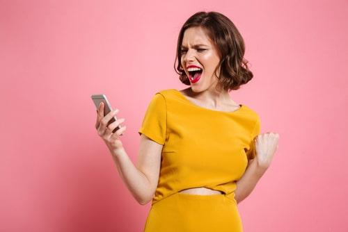 スマートフォンを見ながらガッツポーズをしている女性の様子