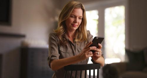 スマートフォンを見て悲しげな表情を浮かべている女性の様子