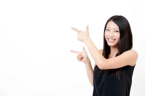 何かに指を指している女性