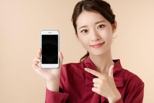 携帯を指指している女性の様子