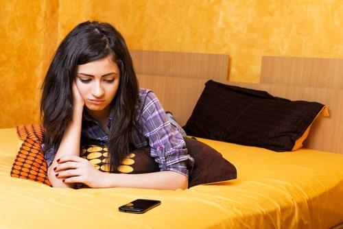 女性が携帯を見つめていやな顔をしている様子