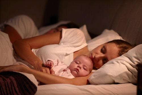 赤ちゃんと一緒に眠りに落ちている女性