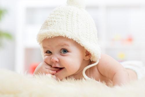 赤ちゃんが指を抱えてこちらを観ている様子