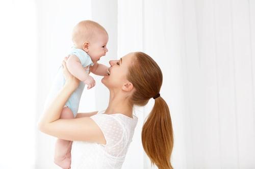 赤ちゃんを抱えて喜んでいる女性