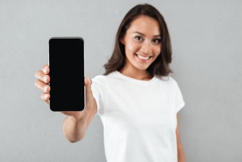 携帯を突きつけて笑みを浮かべている女性