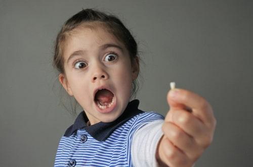 女の子が抜けた歯を持っている様子