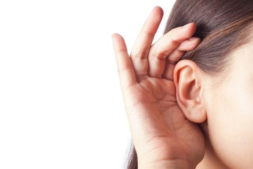 女性が何かに耳をすましている画像