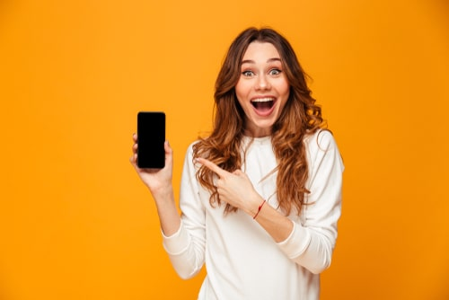 女性が携帯を持っている画像