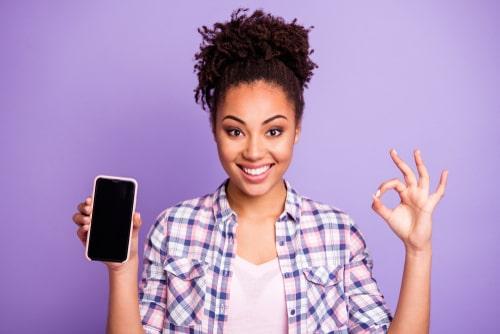 女性がスマートフォンを持っている画像