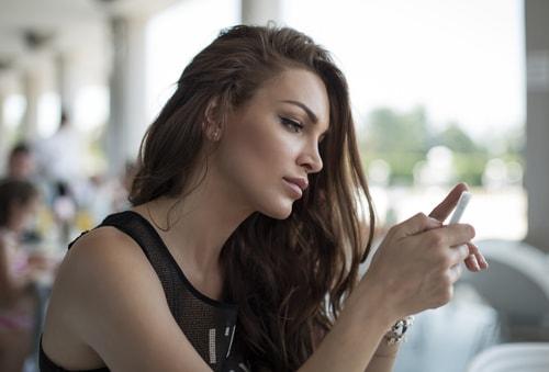 女性が携帯を操作している画像