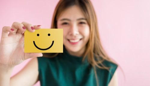 女性がニコちゃんマークを持っている画像