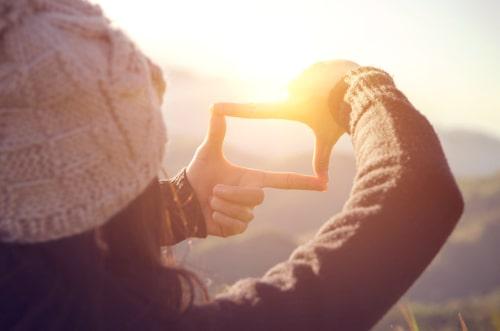 女性が夕日をみている画像