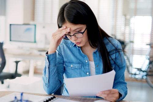 女性が仕事中に頭を抱えている画像