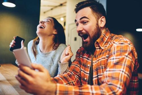 男性と女性がスマホを見て喜んでいる画像