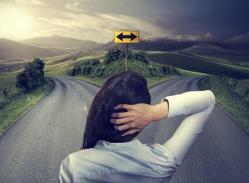 分かれ道で選択を迷っている女性の画像