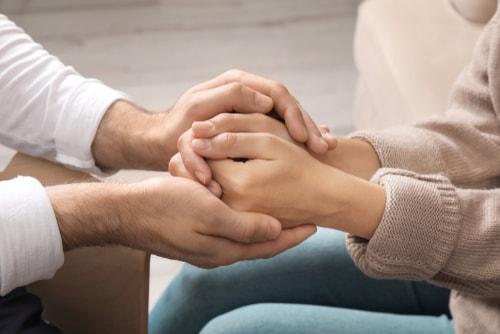 男性が女性の手を握っている画像