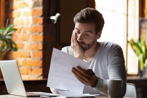 男性が紙を見ながら悲しそうにしている画像