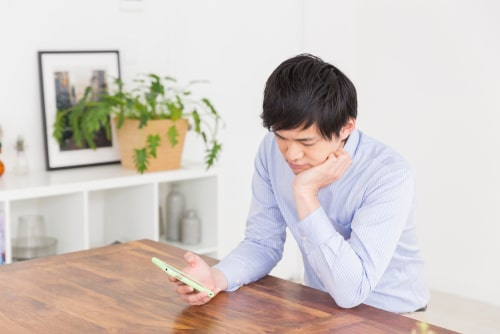 男性がスマートフォンを眺めている画像