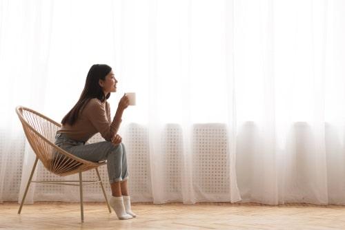 女性がカップを持ちながら座っている画像