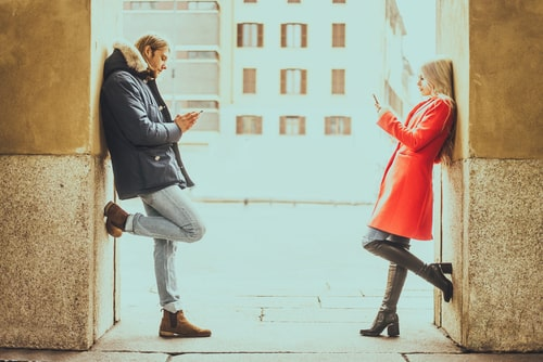 男性と女性が向かい合ってスマホを操作している画像