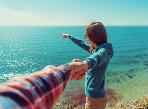 女性が海を指差してウキウキしている画像