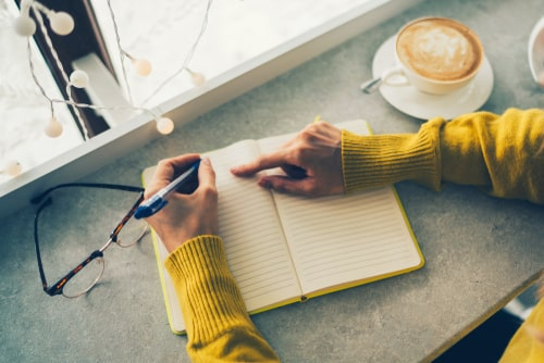 男性がノートにメモをとっている画像
