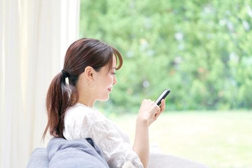 女性がスマホを操作している画像
