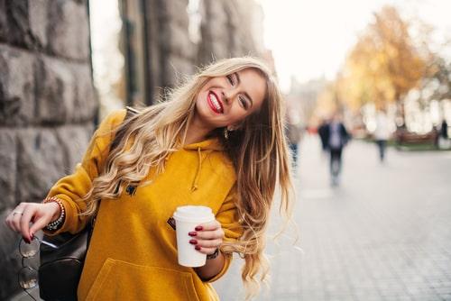 女性が飲み物を持ってこちらに微笑みかけている画像