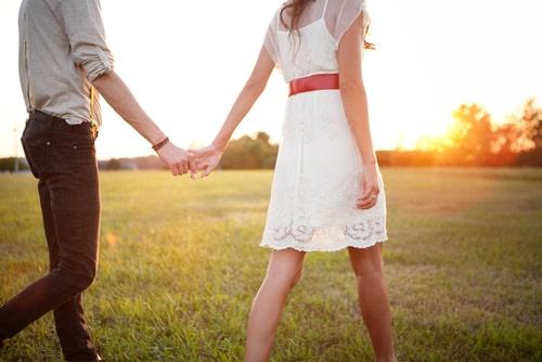 女性と男性が手を繋いでいる画像